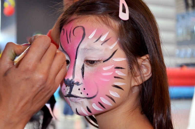Face painting tiger. A pretty little girl having face painting done to turn her into a little tiger stock photos
