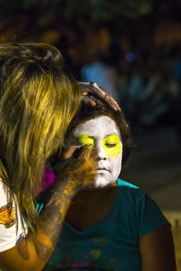 Face Painting. A young girl gets her face painted in preparation for Day of the Dead festivities in Oaxaca, Mexico royalty free stock photography