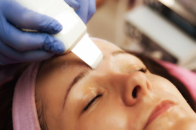 Face peeling. Woman in beauty salon, having her face peeling stock photography