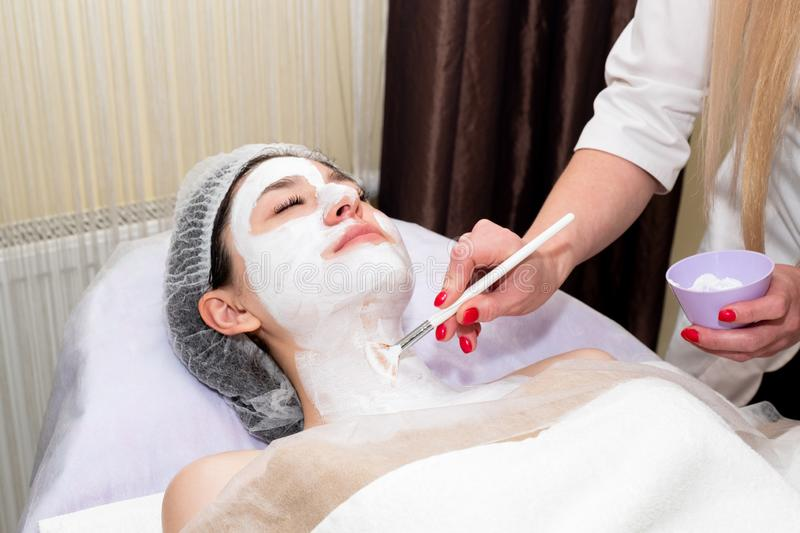 Face peeling mask, spa beauty treatment, skincare. Woman getting facial care by beautician at spa salon royalty free stock images