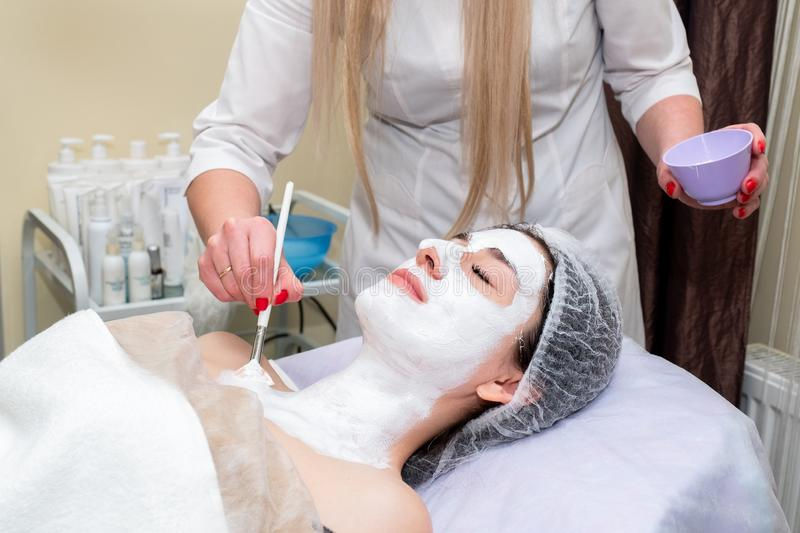 Face peeling mask, spa beauty treatment, skincare. Woman getting facial care by beautician at spa salon stock image