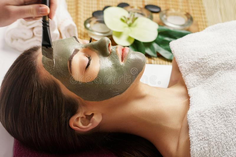 Face peeling mask, spa beauty treatment, skincare. Woman getting facial care by beautician at spa salon,  close-up.Spa clay mask o. N female face stock photography