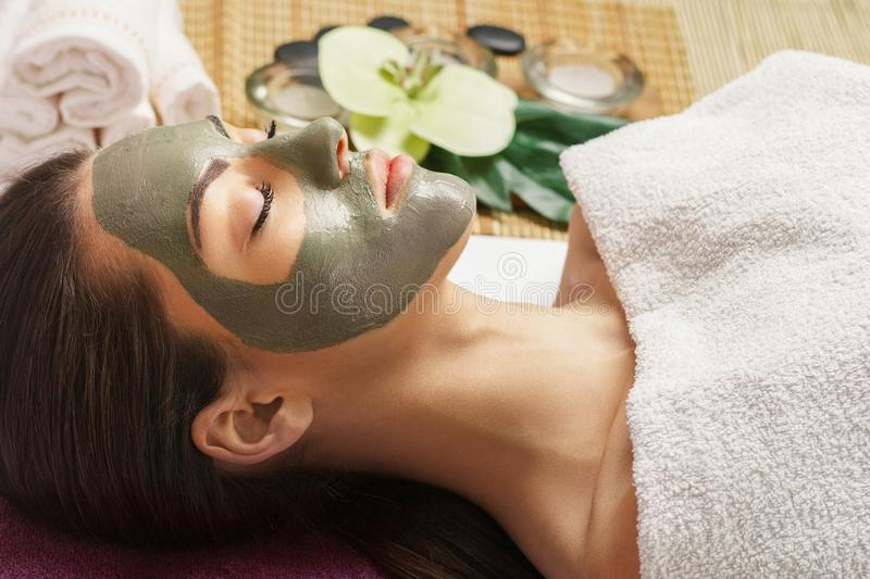 Face peeling mask, spa beauty treatment, skincare. Woman getting facial care by beautician at spa salon,  close-up.Spa clay mask o. N femele face royalty free stock images