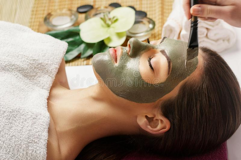 Face peeling mask, spa beauty treatment, skincare. Woman getting facial care by beautician at spa salon, side view, close-up.Spa c royalty free stock photography