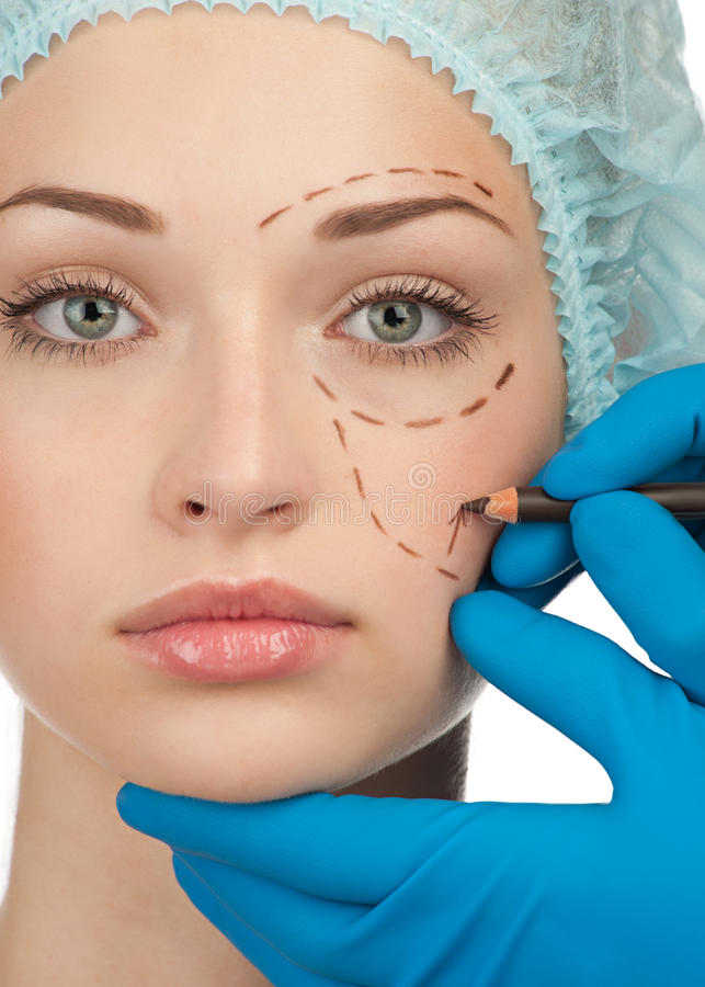 Face before plastic surgery operation. Beautiful young woman with perforation lines on her face before plastic surgery operation. Beautician touching woman face royalty free stock photography
