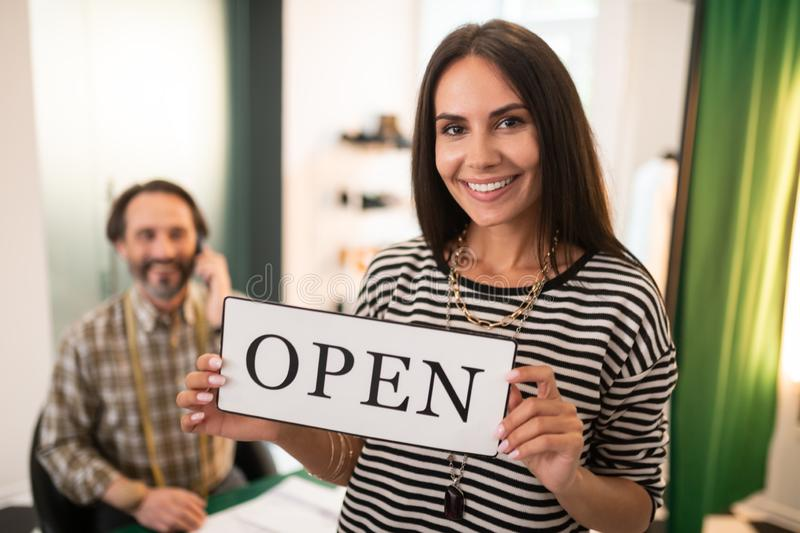Face-portrait of radiant female keeping an open sign in hands stock image