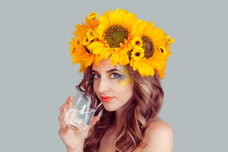 Woman in floral crown from sunflowers drinking water stock photo
