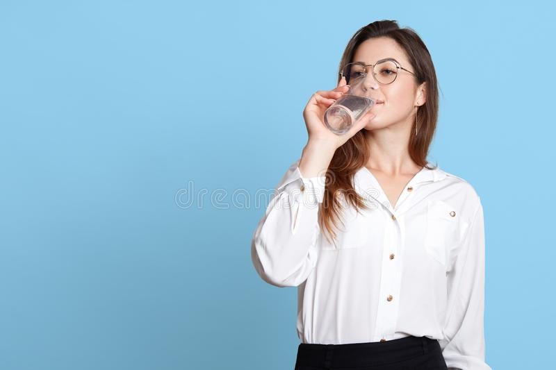 Face portrait of young attractive woman dresses white blouse and black skirt, holds glass in hand and drinks water. Dark haired stock images