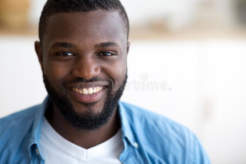 Face portrait of young smiling african american man in office stock photography