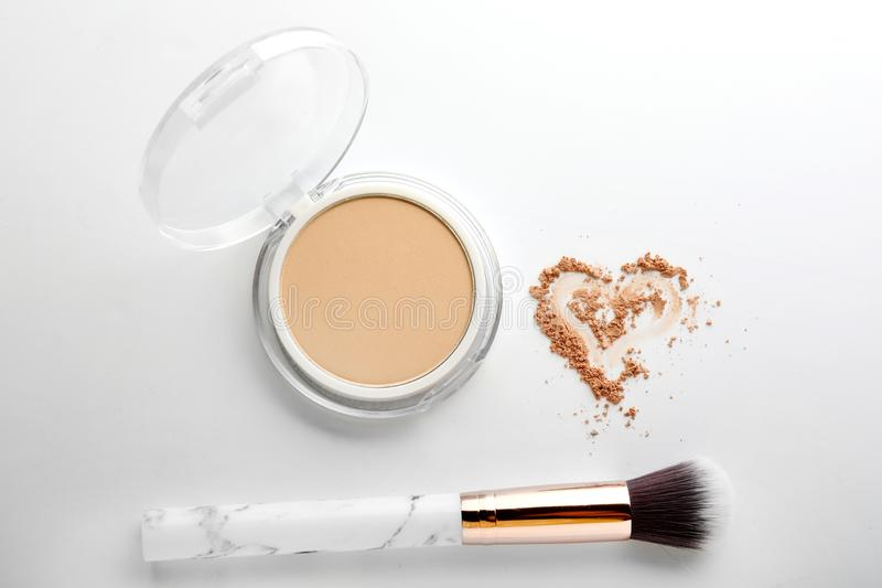 Face powder with brush and drawn heart on white background royalty free stock images