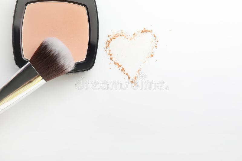 Face powder with brush and drawn heart on white background stock photography