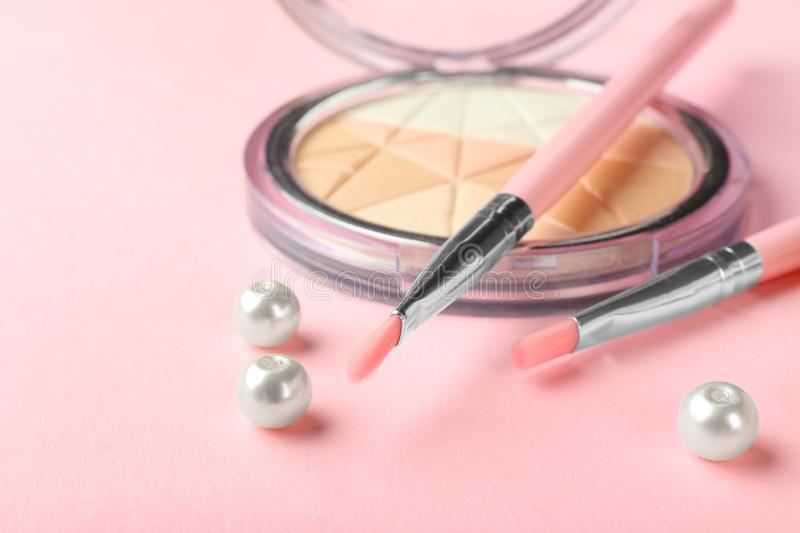 Face powder and brushes on color background. Decorative cosmetics stock image