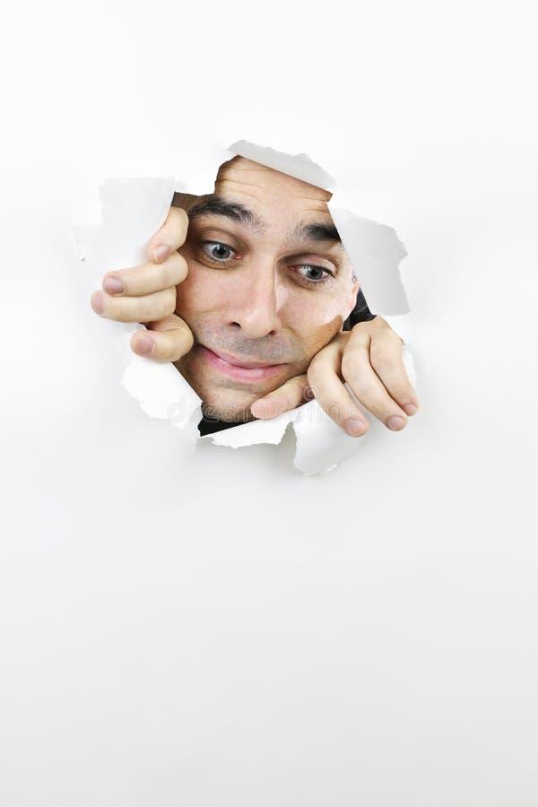 Face que olha através do furo no papel fotografia de stock