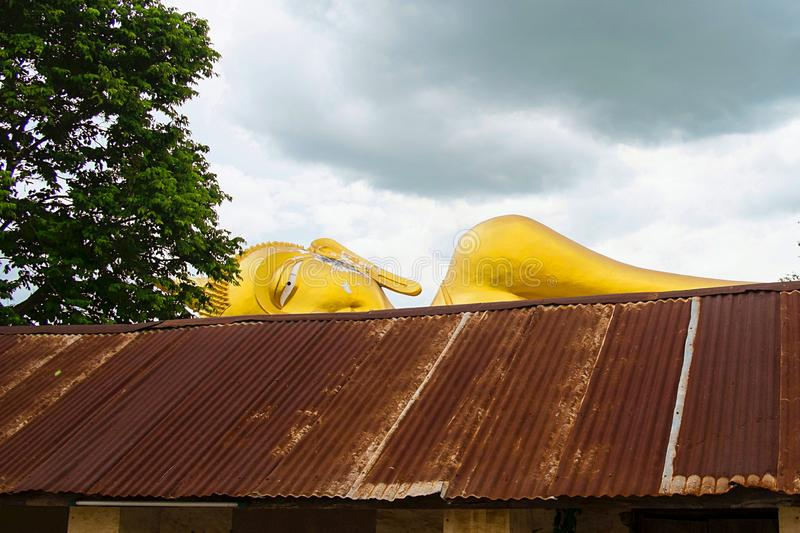 Face of Reclining Buddha behind zinc roof in Buddhist Temple royalty free stock photography