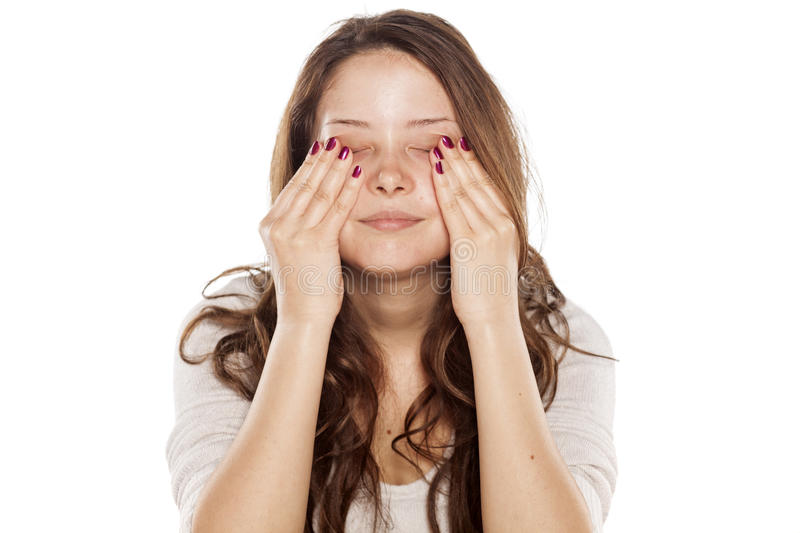 Face rubbing. Young woman without make-up rubbing her face royalty free stock image