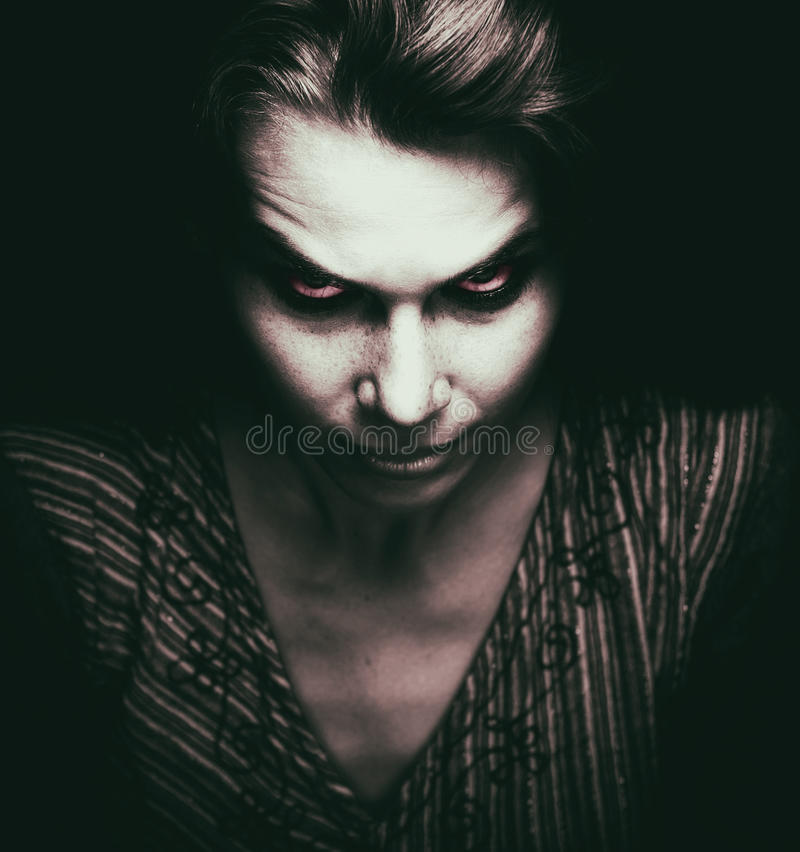 Face of scary woman with evil eyes. In the dark royalty free stock photos