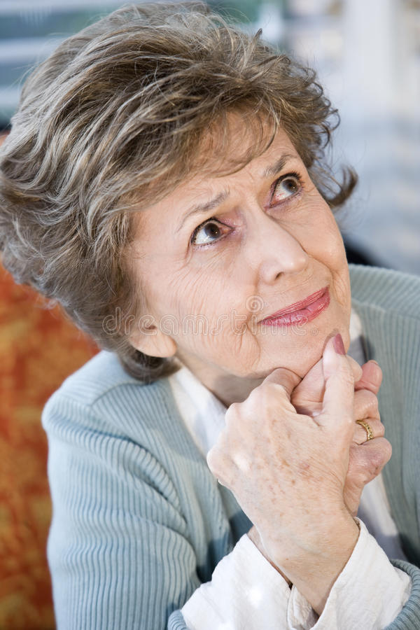 Face of serious elderly woman looking up. Face of elderly woman looking up with serious expression royalty free stock photo