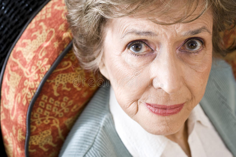 Face of serious elderly woman staring at camera. Face of serious elderly woman in 70s staring at camera royalty free stock images