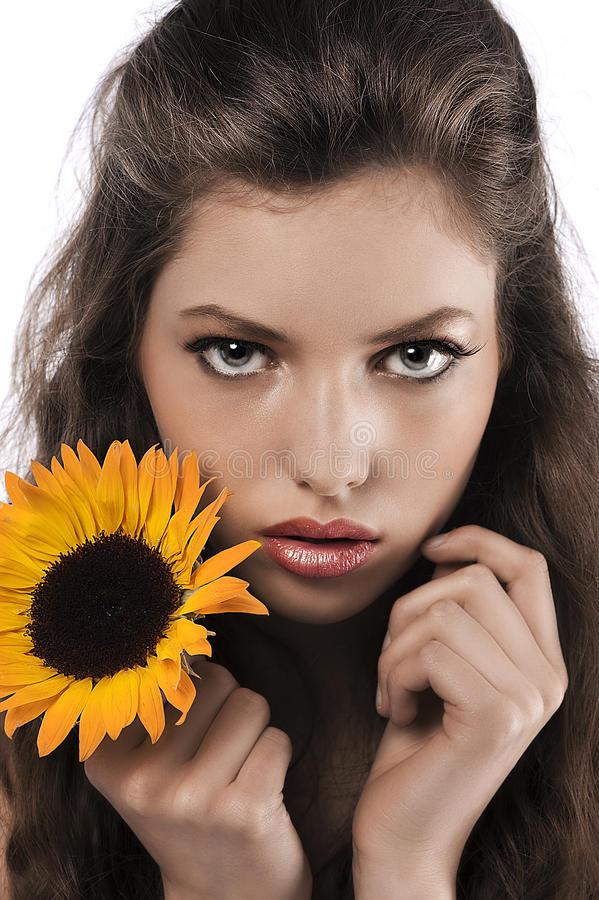 Face shot of a pretty girl holding a sunflower royalty free stock images