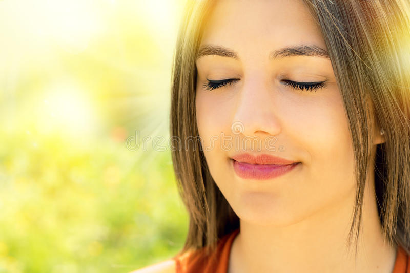 Face shot of relaxed woman meditating outdoors. stock photography