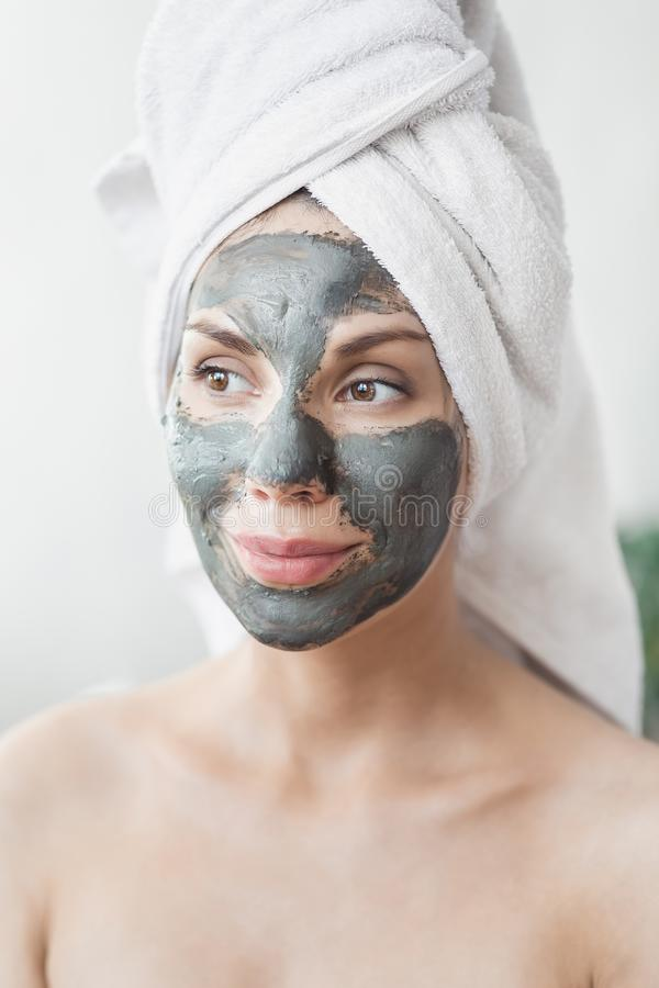 Face Skin care. Attractive Young Woman Wrapped in Bath Towel, applying clay mud mask to face. Skin care concept. Girl royalty free stock photography