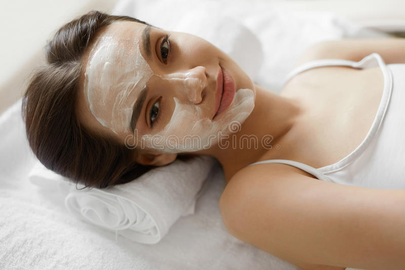 Face Skin Care. Beautiful Woman With Facial Cosmetic Mask At Spa royalty free stock photo