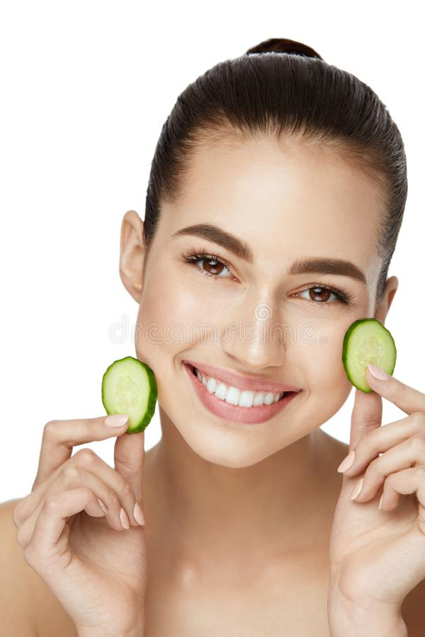 Face Skin Care. Beautiful Woman With Healthy Skin. With Fresh Cucumber Slice In Hands. High Resolution royalty free stock image