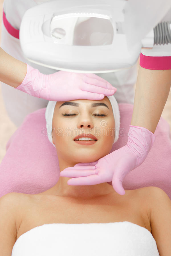 Face Skin Care. Face Lifting. Young woman getting facial massage in the cosmetology salon. Procedure of facial massage in cosmetology. Face Skin Care. Lifting royalty free stock photo