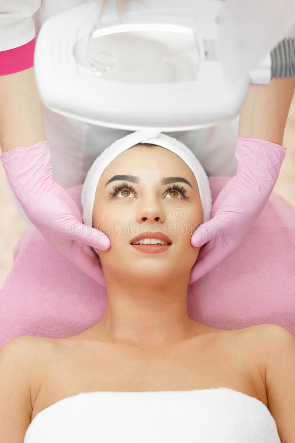 Face Skin Care. Face Lifting. Young woman getting facial massage in the cosmetology salon. Procedure of facial massage in cosmetology. Face Skin Care. Lifting stock photography