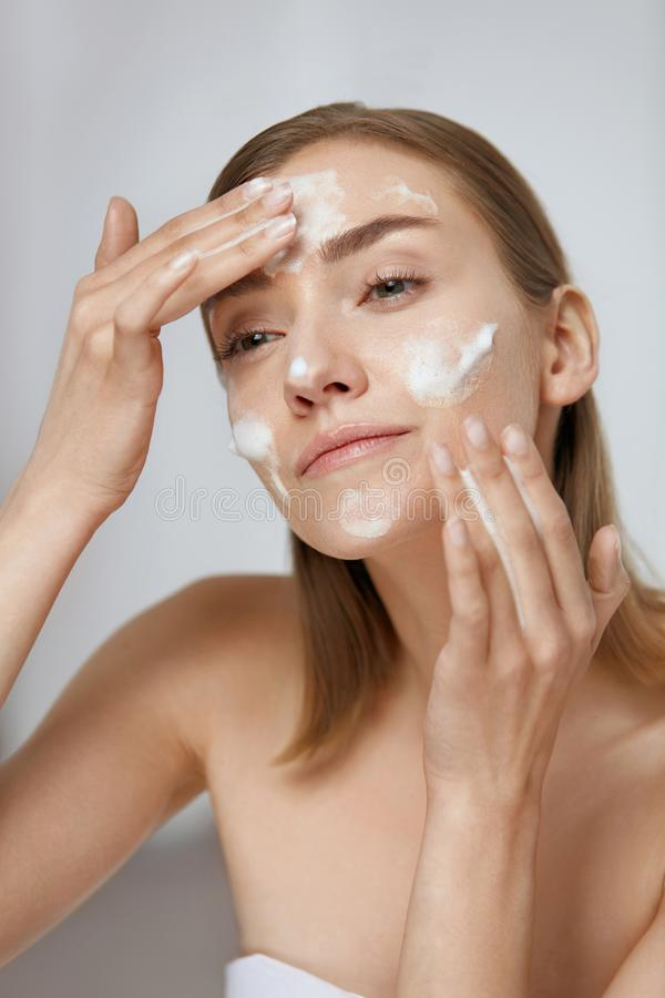 Face skin care. Woman applying facial cleanser on face closeup. Girl using cleansing cosmetic product on skin, washing face on light background stock image