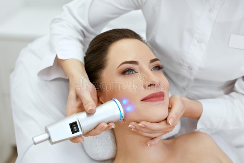 Face Skin Care. Woman Doing Blue Light Therapy At Beauty Clinic royalty free stock photos