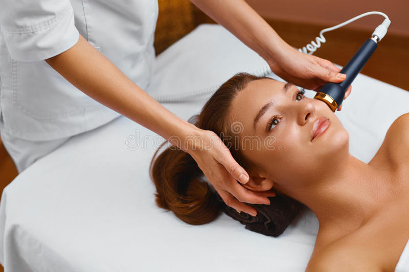 Face skin care. Woman lies on a table in a beauty spa getting a royalty free stock photography