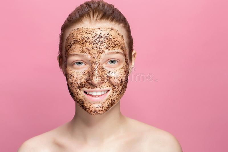 Face Skin Scrub. Portrait Of Smiling Female Model Applying Natural Coffee Mask, Face Scrub On Facial Skin. Closeup. Of Beautiful Happy Woman With Face Covered royalty free stock image