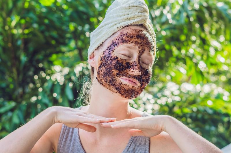 Face Skin Scrub. Portrait Of Smiling Female Model Applying Natural Coffee Mask, Face Scrub On Facial Skin. Closeup Of Beautif. Ul Happy Woman With Face Covered royalty free stock photography