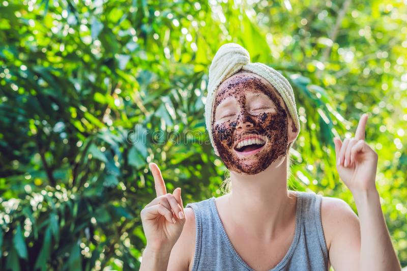 Face Skin Scrub. Portrait Of Smiling Female Model Applying Natural Coffee Mask, Face Scrub On Facial Skin. Closeup. Of Beautiful Happy Woman With Face Covered stock photography