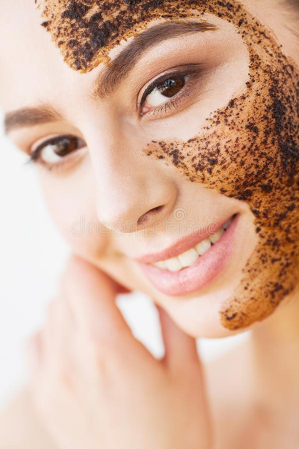 Face Skincare. Young charming girl makes a black charcoal mask o royalty free stock image