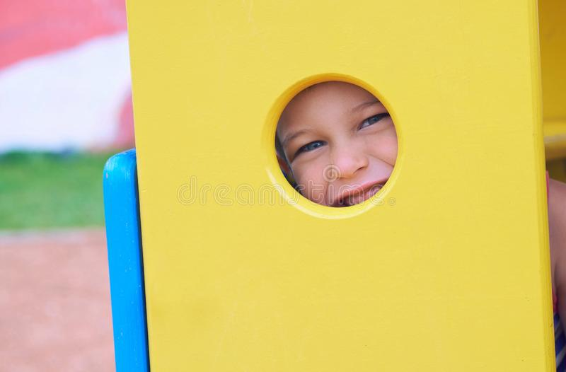 Face of small Caucasian girl looking through a hole in a play equipment outdoors. Orange background. Happy childhood stock photography