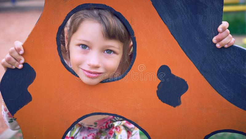Face of small Caucasian girl looking through a hole in a play equipment outdoors. Orange background. Happy childhood. Face of little Caucasian girl looking royalty free stock photo