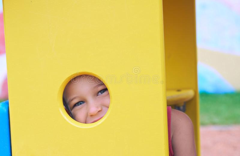 Face of small Caucasian girl looking through a hole in a play equipment outdoors. Orange background. Happy childhood royalty free stock photos