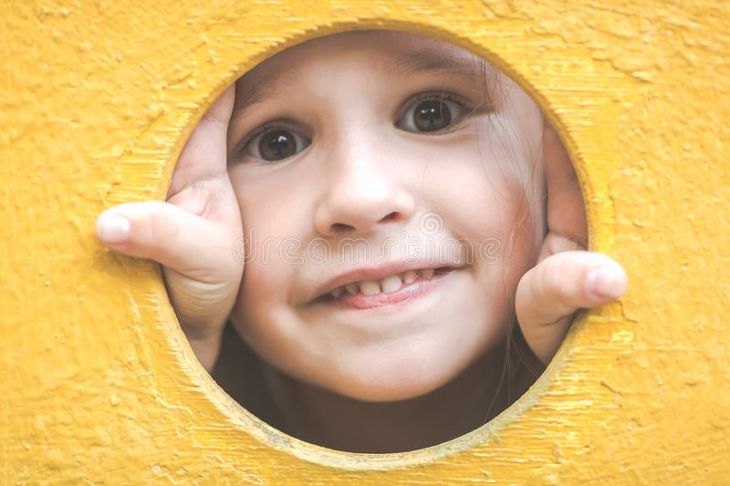 Face of small child girl looking through a hole in a play equipment outdoors. Yellow background. Happy childhood concept. Face of small child girl looking royalty free stock image