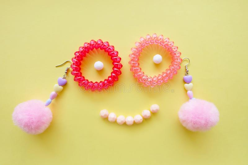Face Smile Spiral Rubber Bands Fashion Accessories. Pink Heart Earring Isolated of Different Color Bead on Yellow Background. Great For Any Use royalty free stock images