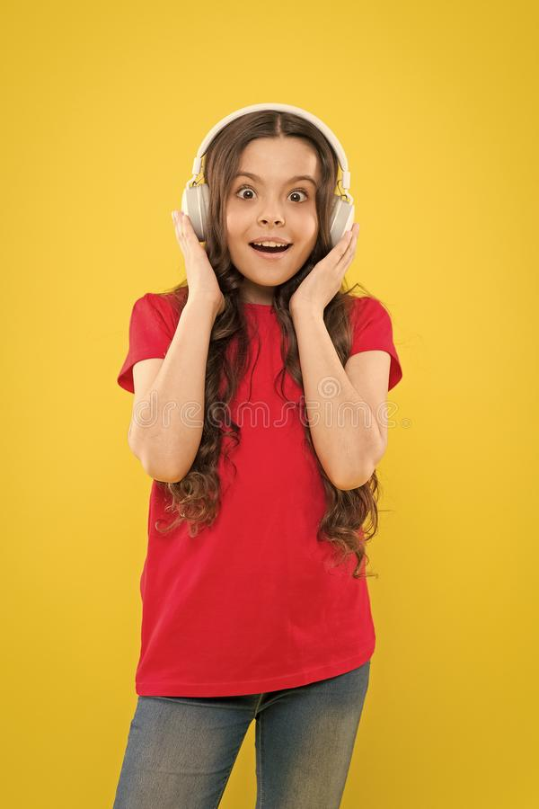 Face the sound. Adorable little girl listening to sound track on yellow background. Cute small child wearing headphones. Playing electronic sound. Relaxing with stock photography