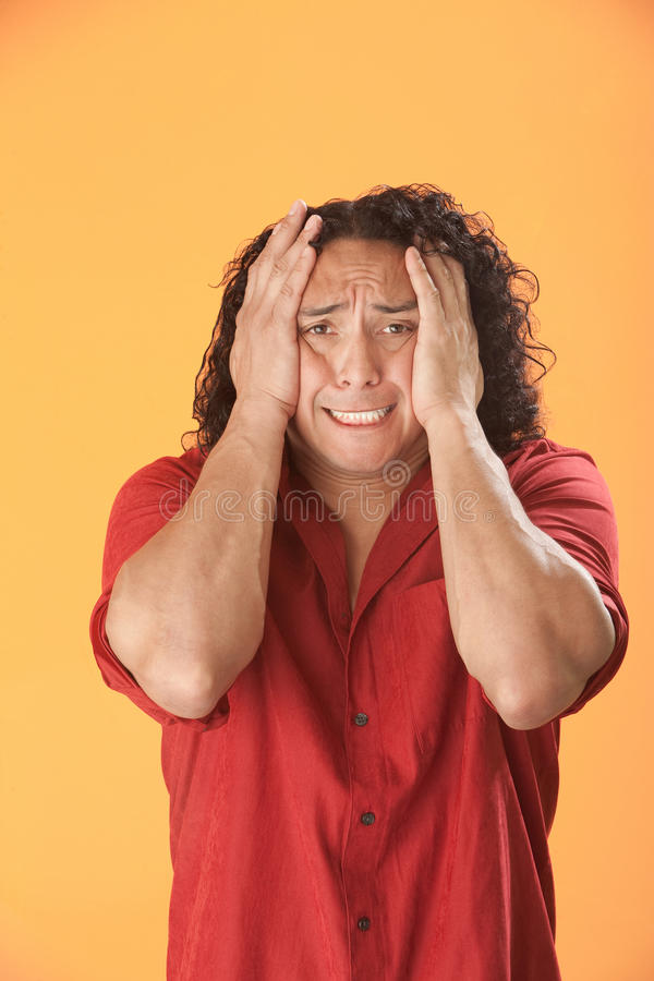 Face Squeeze. Young Hispanic man squeezes his own head royalty free stock photo