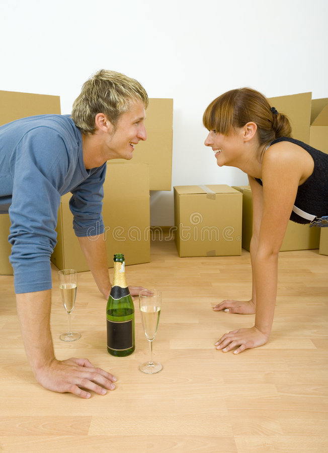 Face to face. Young couple kneeling on the floor in flat. They're looking happy. Celebrating removal with champagne. Looking at each other royalty free stock photography