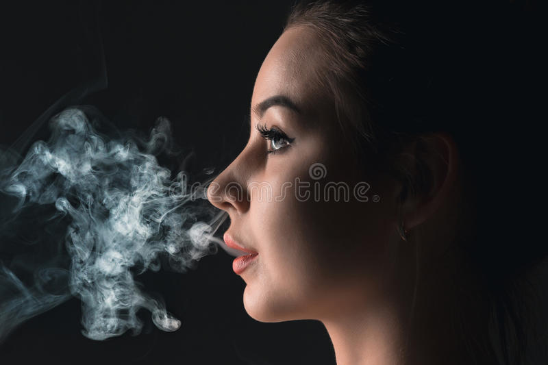 The face of vaping young woman at black studio. The face of vaping young woman on black studio background stock photography
