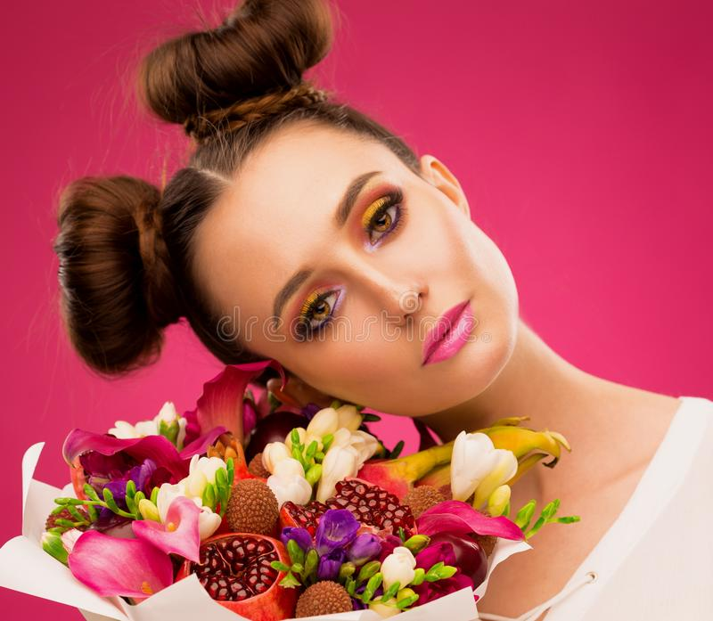Face woman, fruit bouquet, pink. Beautiful face woman, has eyes, lips, decorative pink make up, holds luxury fruit flowers bouquet: pink callas, garnet, lychees stock photos