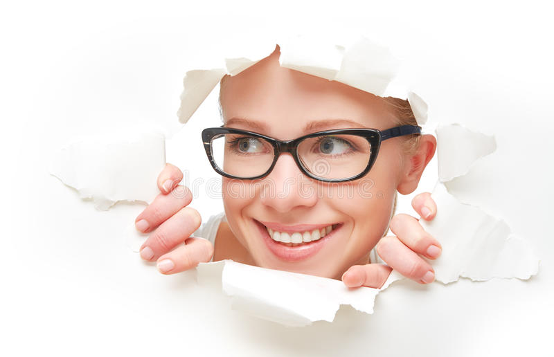 Face of woman in glasses peeking through a hole torn in white paper poster. Face of a young curious woman in glasses peeking through a hole torn in white paper stock photo