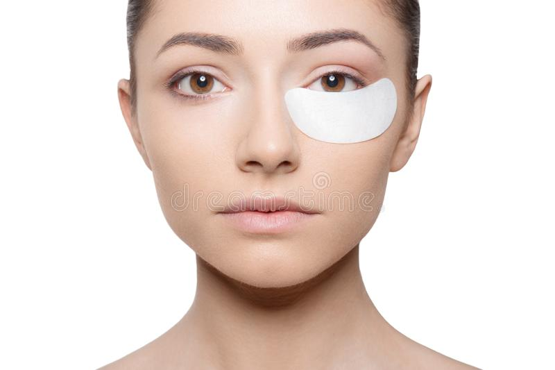 Woman applying her plaster under her eye during make up, isolated on white background. Horizontal view royalty free stock image