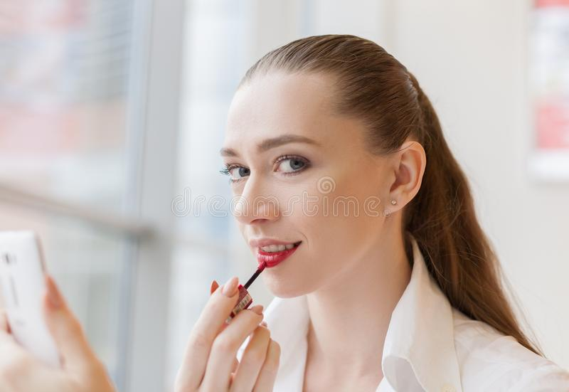 Face woman, paints lips lipstick stock images