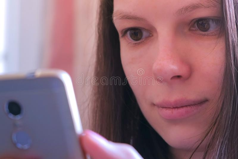 Face woman reads book on smartphone online browsing surfing online internet. Portrait of young woman is reading book on smartphone, browsing internet pages stock photos